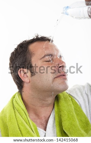 man pouring water on himself to cool down after after sports. Male fitness concept. - stock photo