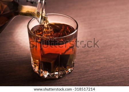 Man pouring whiskey on glass. Alcohol beverage background.