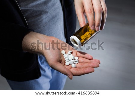 Man pouring white pills into his hand - stock photo