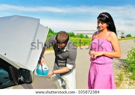 Man pours a liquid for washing glasses to the car - stock photo