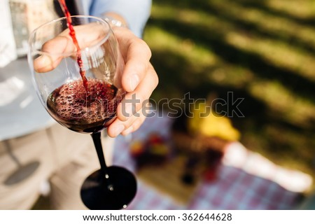 Man pours red wine in glass at the picnic. Couple have a romantic date. - stock photo