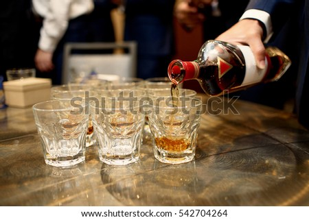 Man pours whisky in crsytal glasses standing on the wooden table