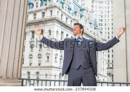 Man Power. Dressing in dark blue three piece suit, necktie, a handsome, sexy, middle age businessman is standing outside office building, stretching two arms, symbol of success. - stock photo