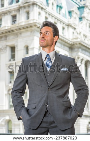 Man Power. Dressing in dark blue three piece suit, necktie, hands in pockets, a handsome, sexy, middle age businessman is standing outside office building, confidently looking up. - stock photo