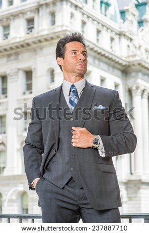 Man Power. Dressing in dark blue three piece suit, necktie, holding a fist, a handsome, sexy, middle age businessman is standing outside office building, confidently looking up.  - stock photo