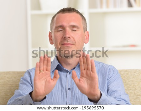 Man practicing Reiki transfering energy through palms, a kind of energy medicine. - stock photo