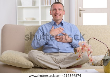 Man practicing self Reiki transfering energy through palms, a kind of energy medicine. - stock photo