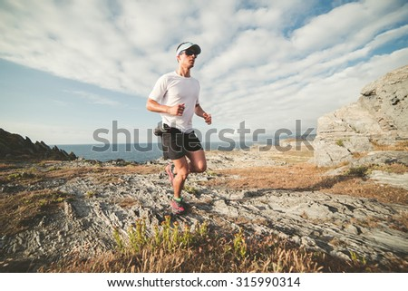 Man practicing trail running in a landscape of the coast - stock photo