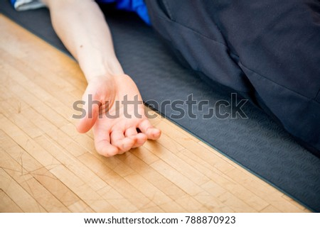 Man practicing yoga indoors in a retreat space doing Corpse Pose - Savasana - closeup of a hand