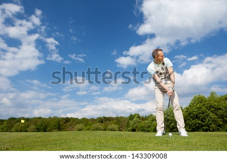 man practising golf on a sunny day - stock photo