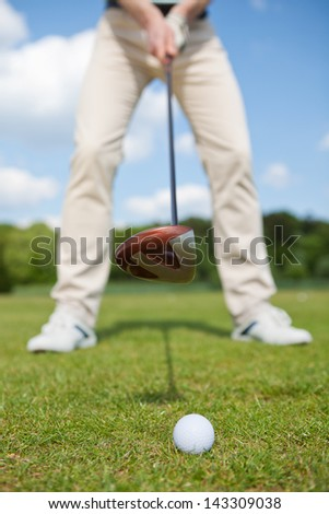 man practising golf with golf club in foreground