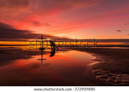 Man praying at a cross on a beach with a wonderful sunset sky behind him. - stock photo