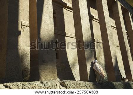 Man praying at Bete Medhane Alem, Rock Hewn Churches, Lalibela - stock photo