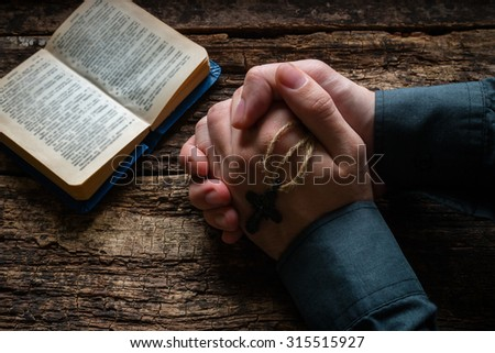 man praying before a bible selective focus