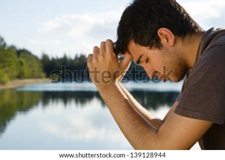 Man Praying by Lake - stock photo