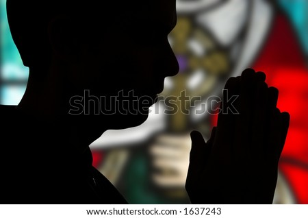 Man praying in front of stained glass window - stock photo