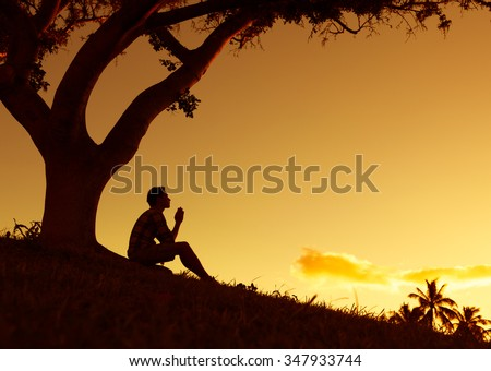 Man praying, meditating in harmony and peace at sunset - stock photo