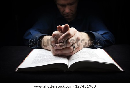Man praying to God with his hands resting on a bible. - stock photo