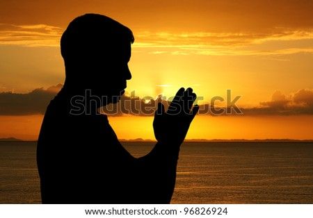 Man praying with his hands folded at sunset - stock photo