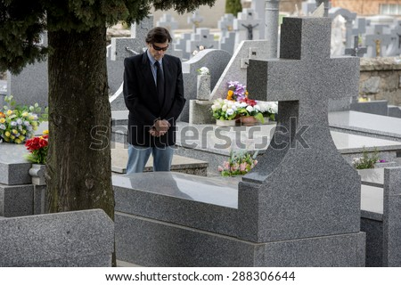 Man prayingin the the tomb of a cemetery