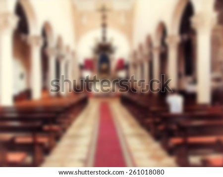Man prays in empty church. Blur and vintage instagram filters applied. - stock photo