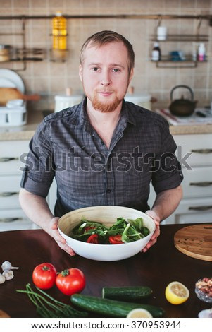 man prepares vegetarian salad in the kitchen - stock photo