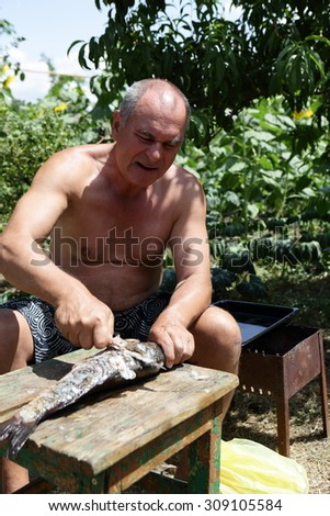 Man preparing a fish for cooking outdoor