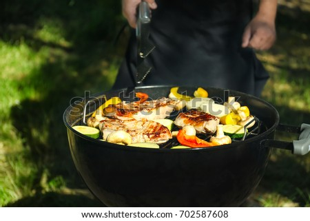 Man preparing barbecue steaks with vegetables on grill