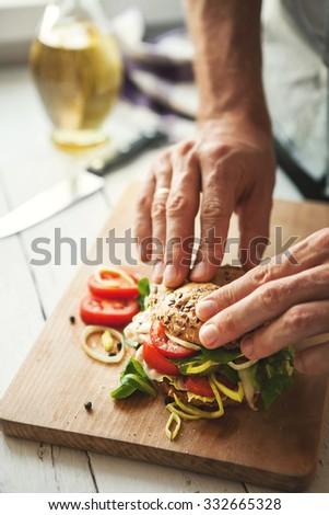 Man preparing big sandwich - stock photo