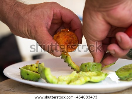 Man preparing cactus fruits to eat, hands fragment photo close up