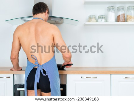 Man preparing food in the kitchen. View from the back. - stock photo