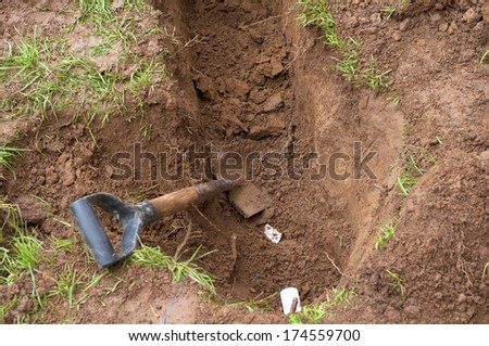 Man Preparing Hole in Ground for Installation of New PVC Pipes for in ground Sprinkler System in a Yard  - stock photo
