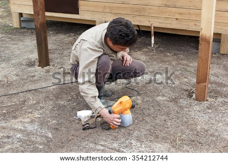 man preparing spray gun for painting wooden structure
