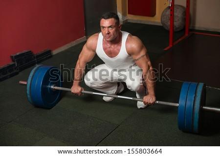 Man preparing to do deadlift - stock photo