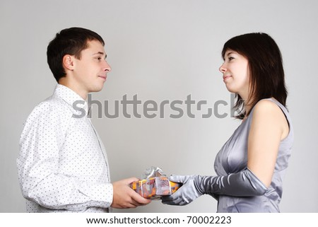 man present gift to brunette woman in evening dress, looking to each other - stock photo