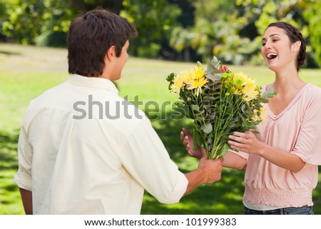 Man present his surprised friend with a bouquet of flowers in a park