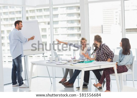 Man presenting an idea to his colleagues in creative office - stock photo