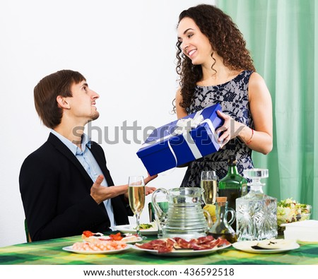 Man presenting gift to smiling woman during romantic dinner with champagne in home. Focus on woman - stock photo