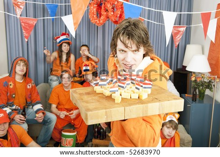 Man presenting his friends with a few snacks during a soccer game on television - stock photo