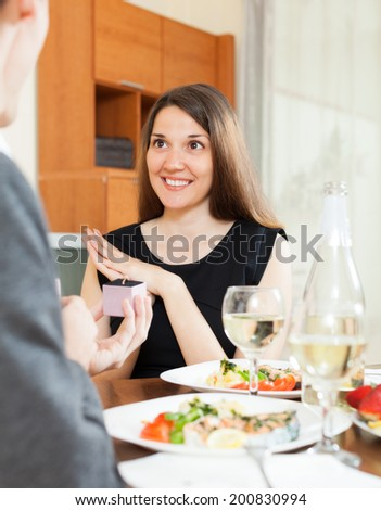 Man presenting to amazed pretty girl ring in box  at table