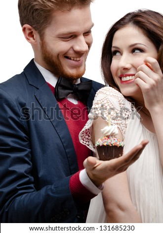 Man presents birthday cake to his pretty girlfriend who likes it very much, isolated on white - stock photo