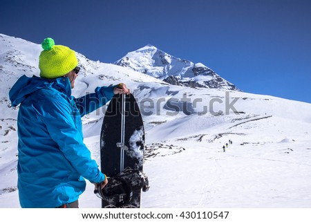 Man presents his splitboard, in the background can be seen walking on top of the mountain freeriders
