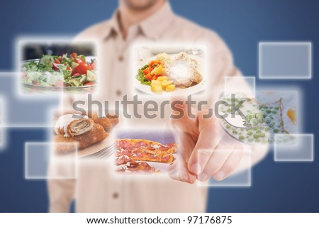 Man pressing a touchscreen button, with food selection - stock photo