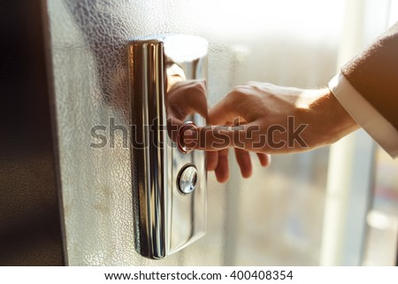 Man pressing elevator button. finger presses the elevator button. Red button. sunset light. businessman is a lift. high floor. hand reaches for the button of the elevator call. - stock photo