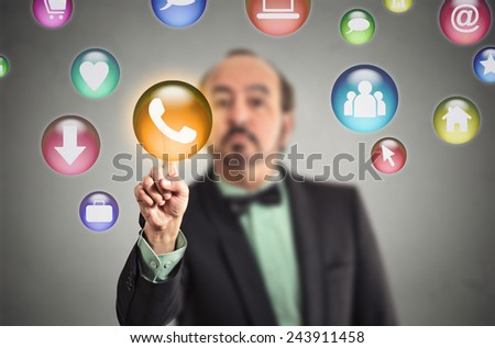 Man pressing modern social media buttons on touch screen. Communication technology mobile phone high tech concept. Colorful touchscreen multimedia symbols on grey background, focus on phone call icon - stock photo