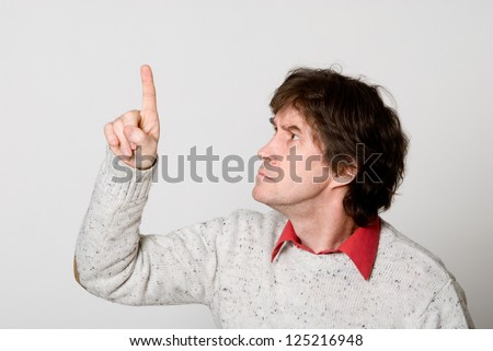 Man pressing / pushing button isolated on light background. Caucasian male in his 40s - stock photo