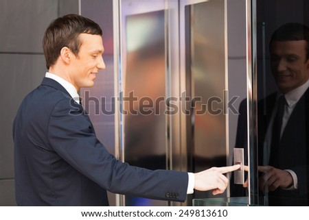 Man pressing red elevator button. side view of businessman pushing elevator button  - stock photo