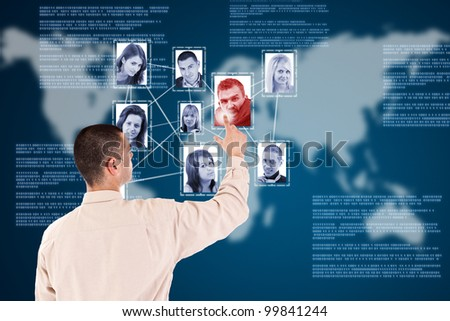 Man pressing Social network pictures in digital futuristic blue background - stock photo