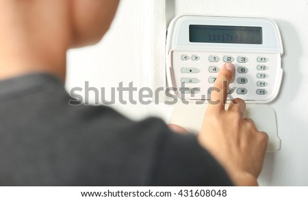 Man pressing the code on a house alarm - stock photo