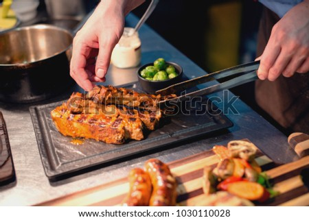Man pripering lunch with grilled meat and vegetables, cut out.